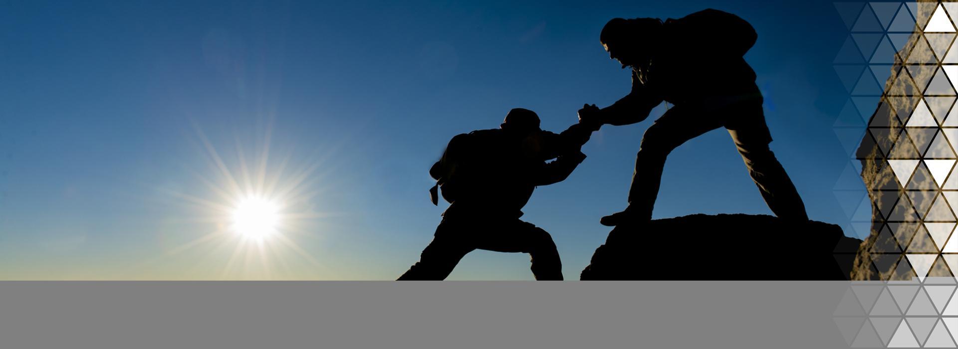 Zaufanie-dwóch ludzi wspinających się na szczyt.